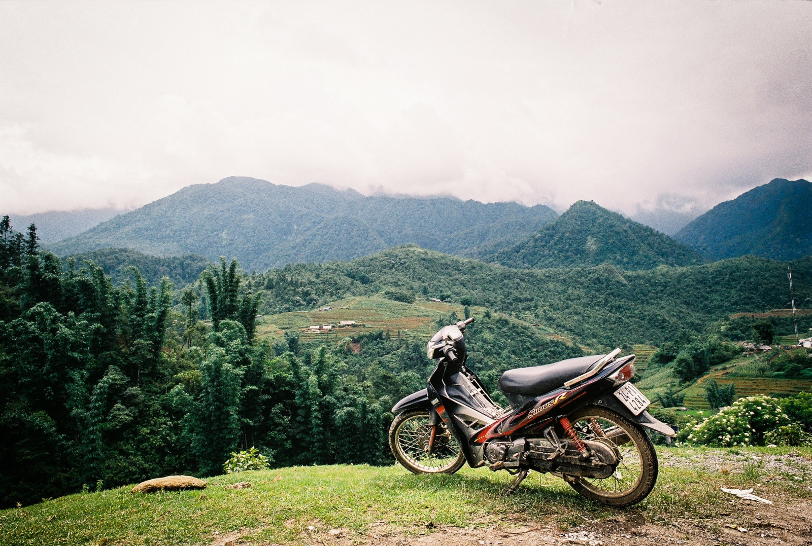 Image of a motorbike parked in front of the mountains in Sapa, Vietnam