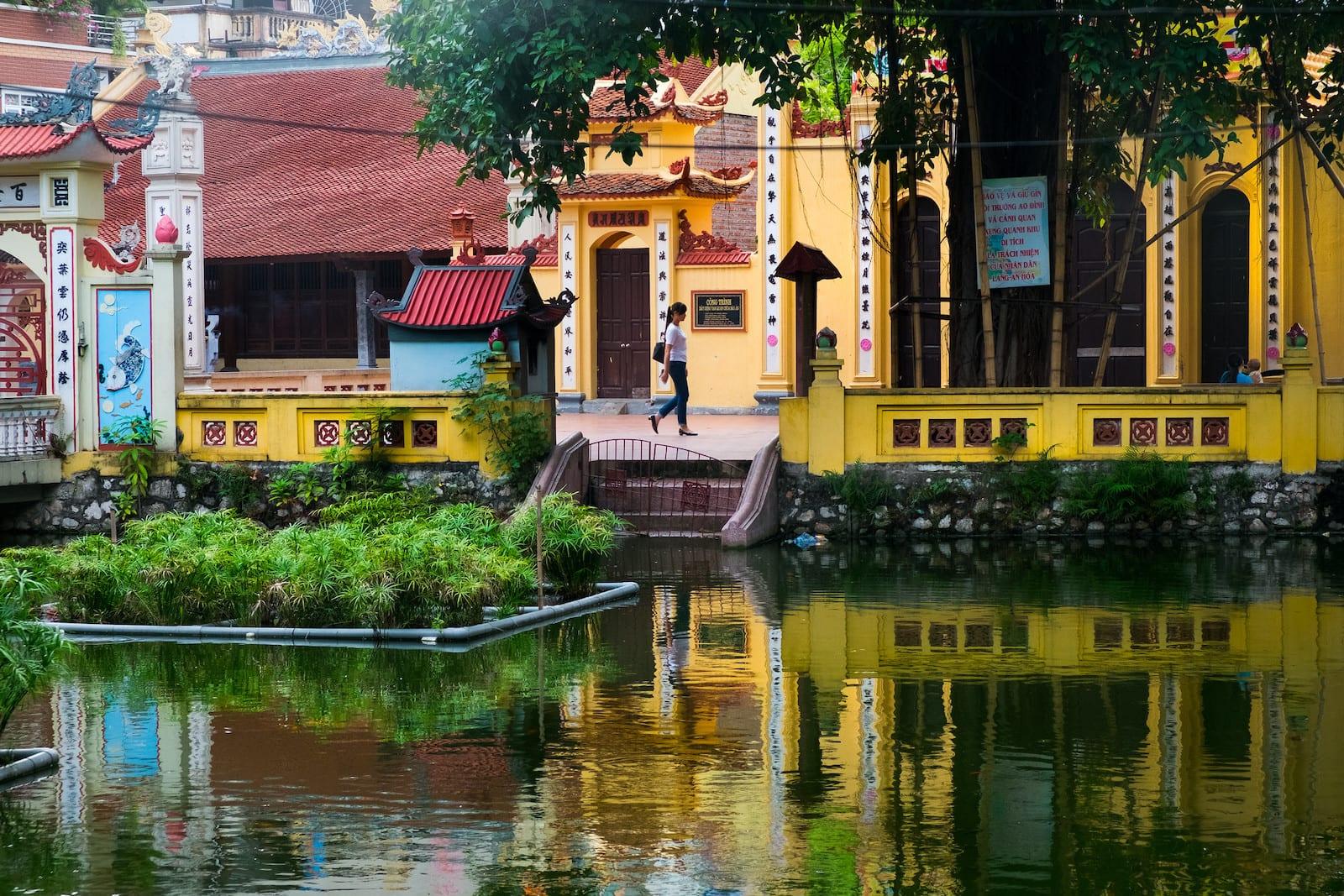 Vietnamese woman walking though the temple at Cong Vien, Cau Giay, Hanoi