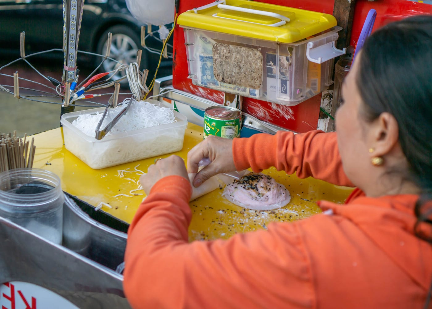 Woman rolling Bo Bia Dessert at a Street Food Cart in Saigon