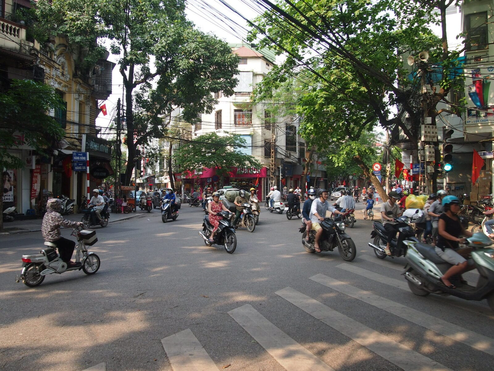 Image of motorbike riders zipping through the streets in Hanoi