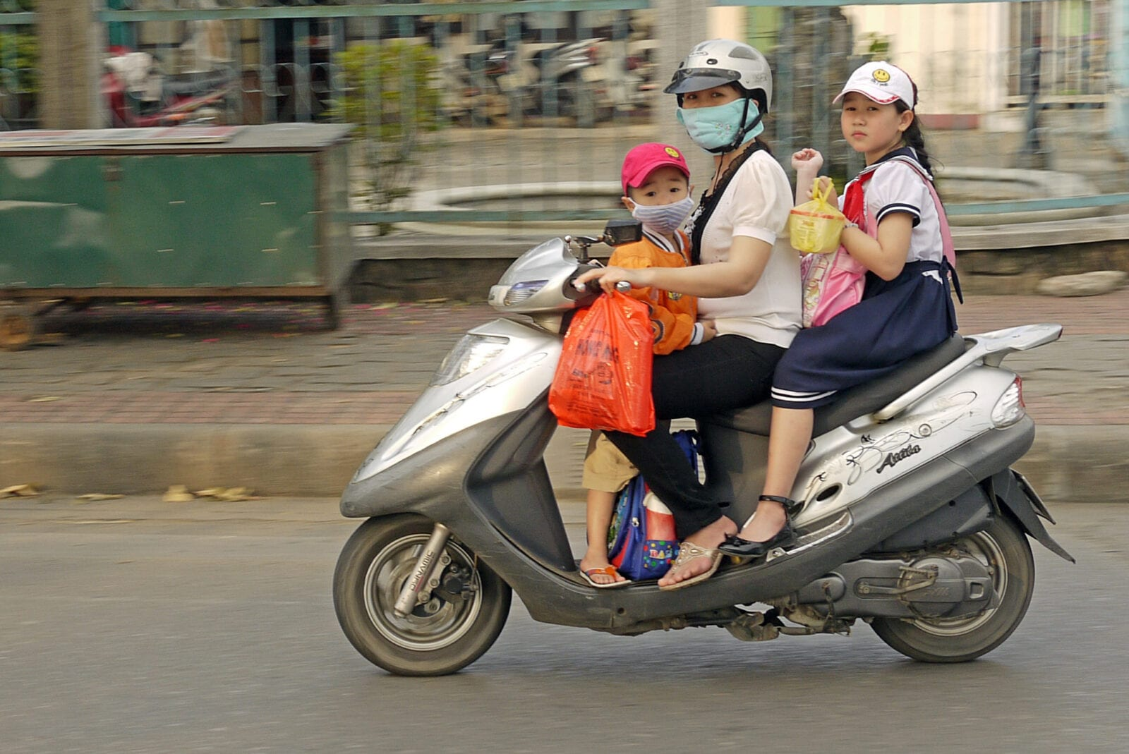 Image of a mother and her children riding on a motorbike