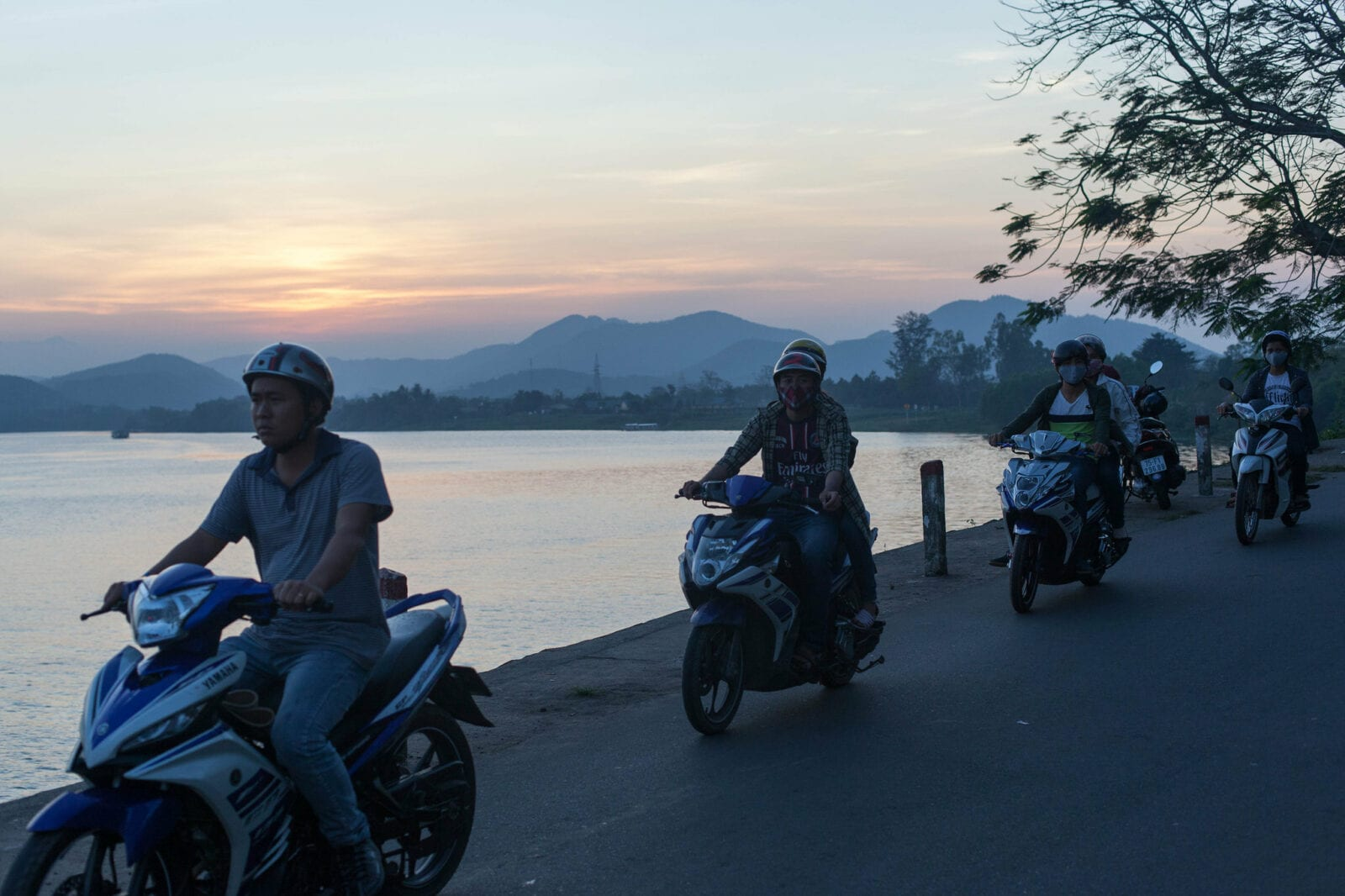 Image of motorbike riders on the waterfront in vietnam