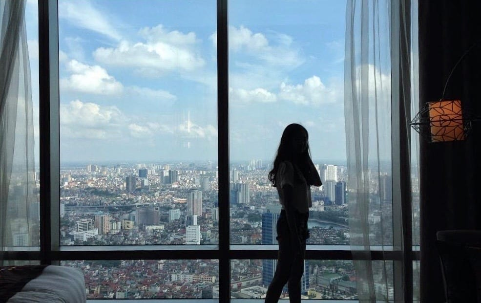 Image of a woman standing in front of a window at the Lotte Hotel Hanoi in Vietnam