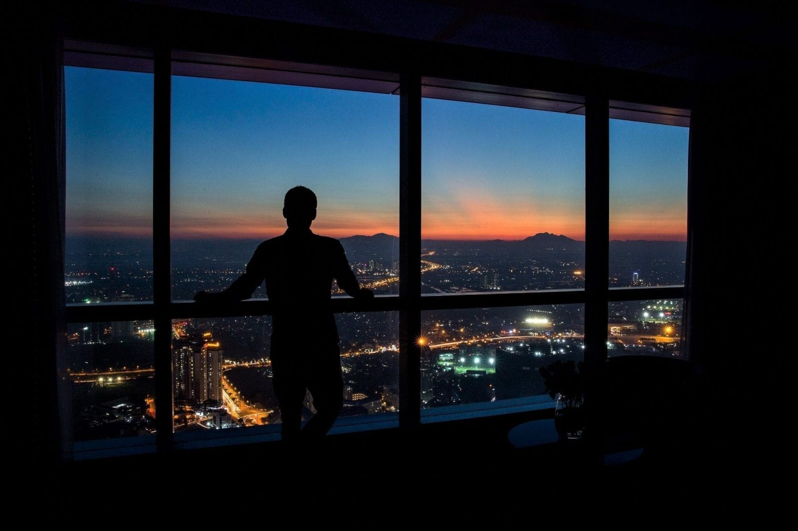 Image of a man looking out the window at the sun setting over Hanoi from the InterContinental at Landmark 72