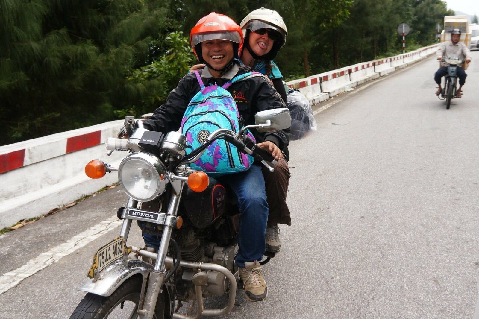 Image of a local taking a tourists on a motorcycle tour from Hoi an to Hue in Vietnam
