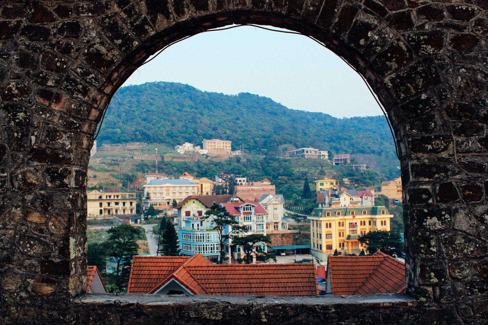 Image of Tam Dao looking through a stone window in Vietnam