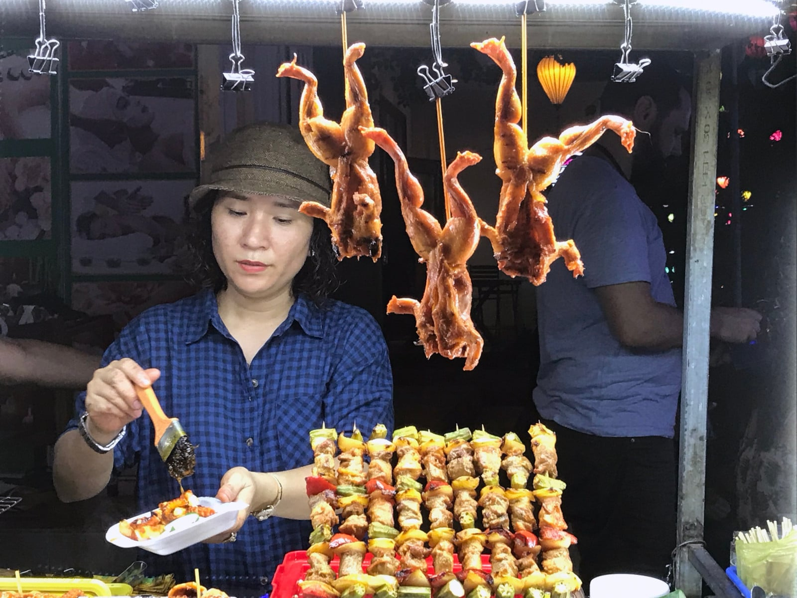 Image of a woman at a chicken stall at the Hoi An Night Market in Vietnam