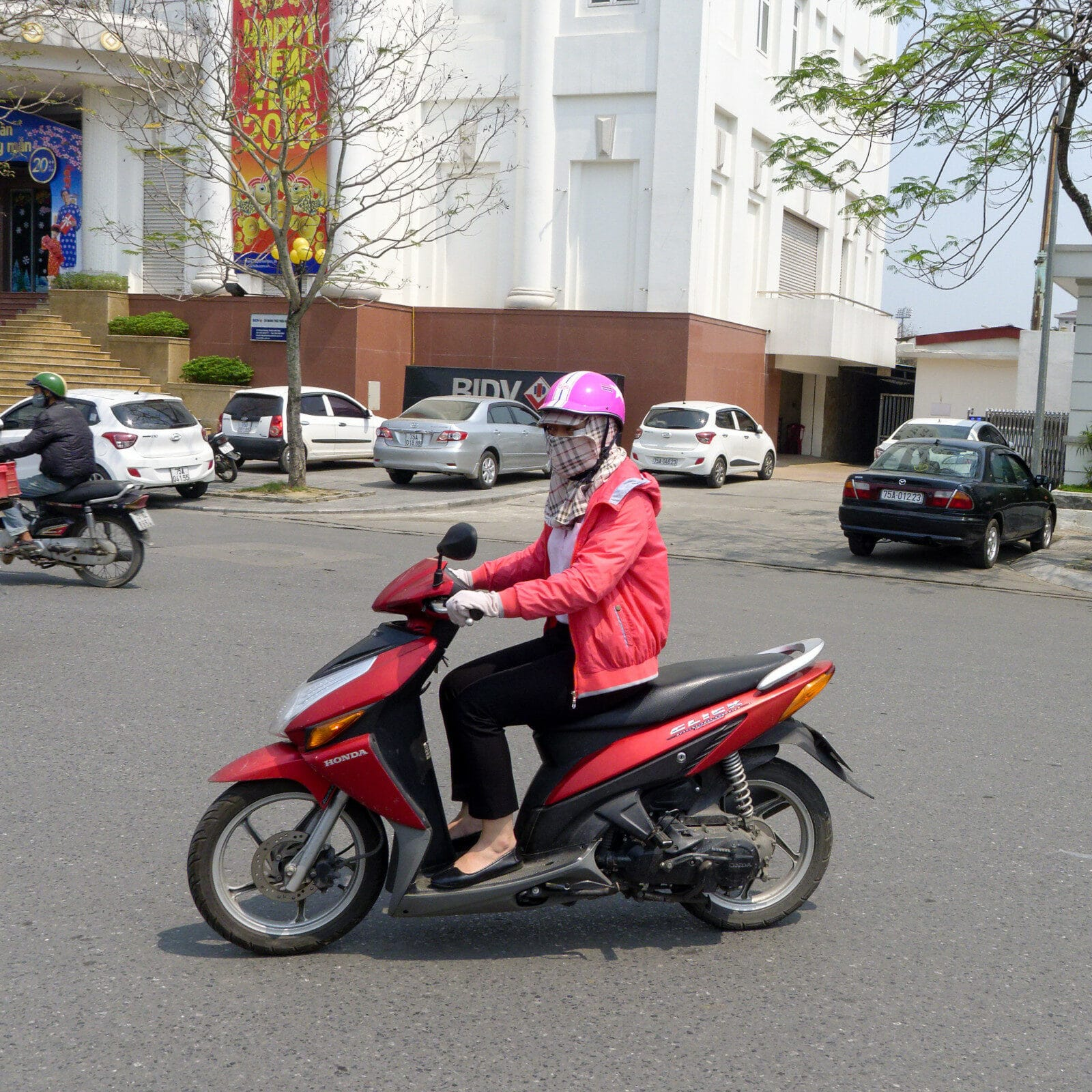 Image of a woman wearing pink on a pink motorbike in Vietnam