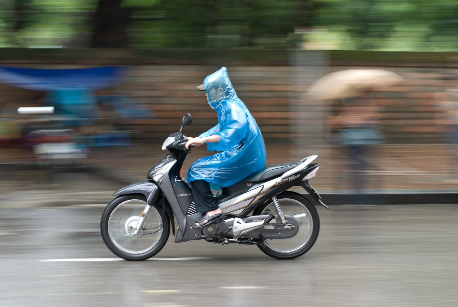 Image of a person on a motorbike in Vietnam wearing a rain pancho