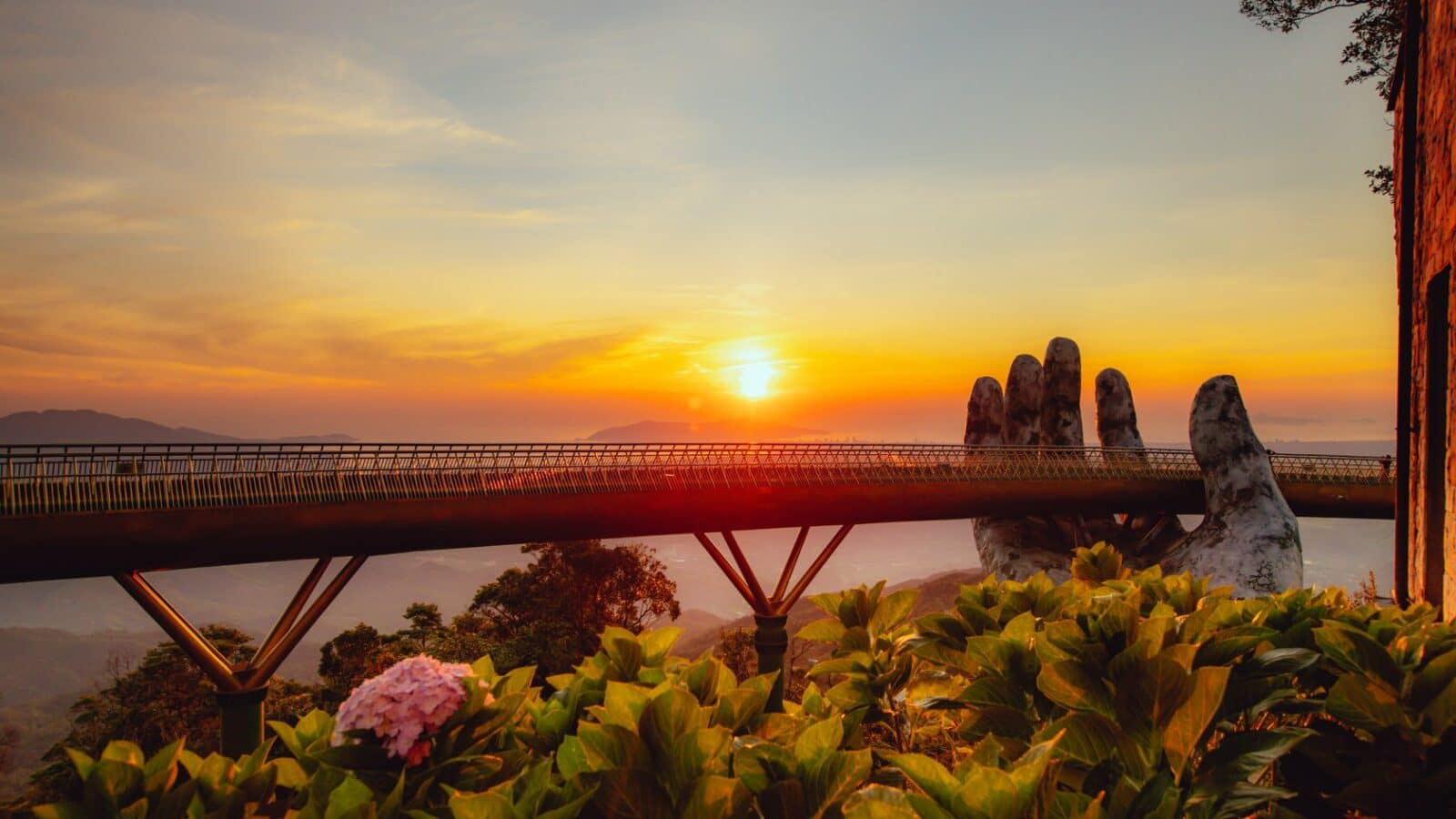 Image of the sun setting behind the golden bridge at sunworld Ba na hills in Da nang