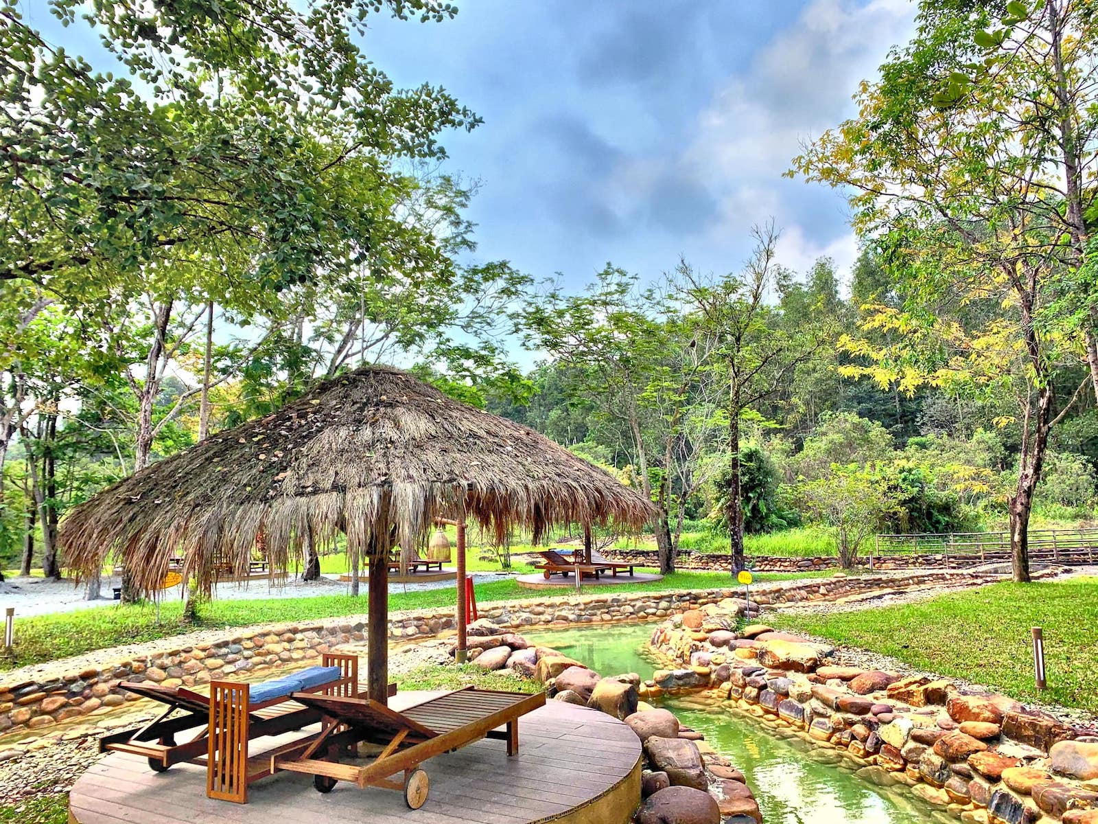 Image of the hot springs stream and lounge area at Alba Wellness Valley in Hue, Vietnam