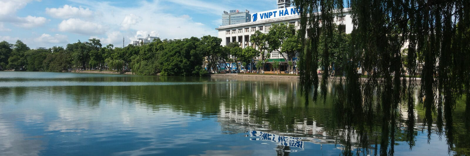 Image of the post office reflecting on Hoan Kiem Lake in Hanoi, Vietnam