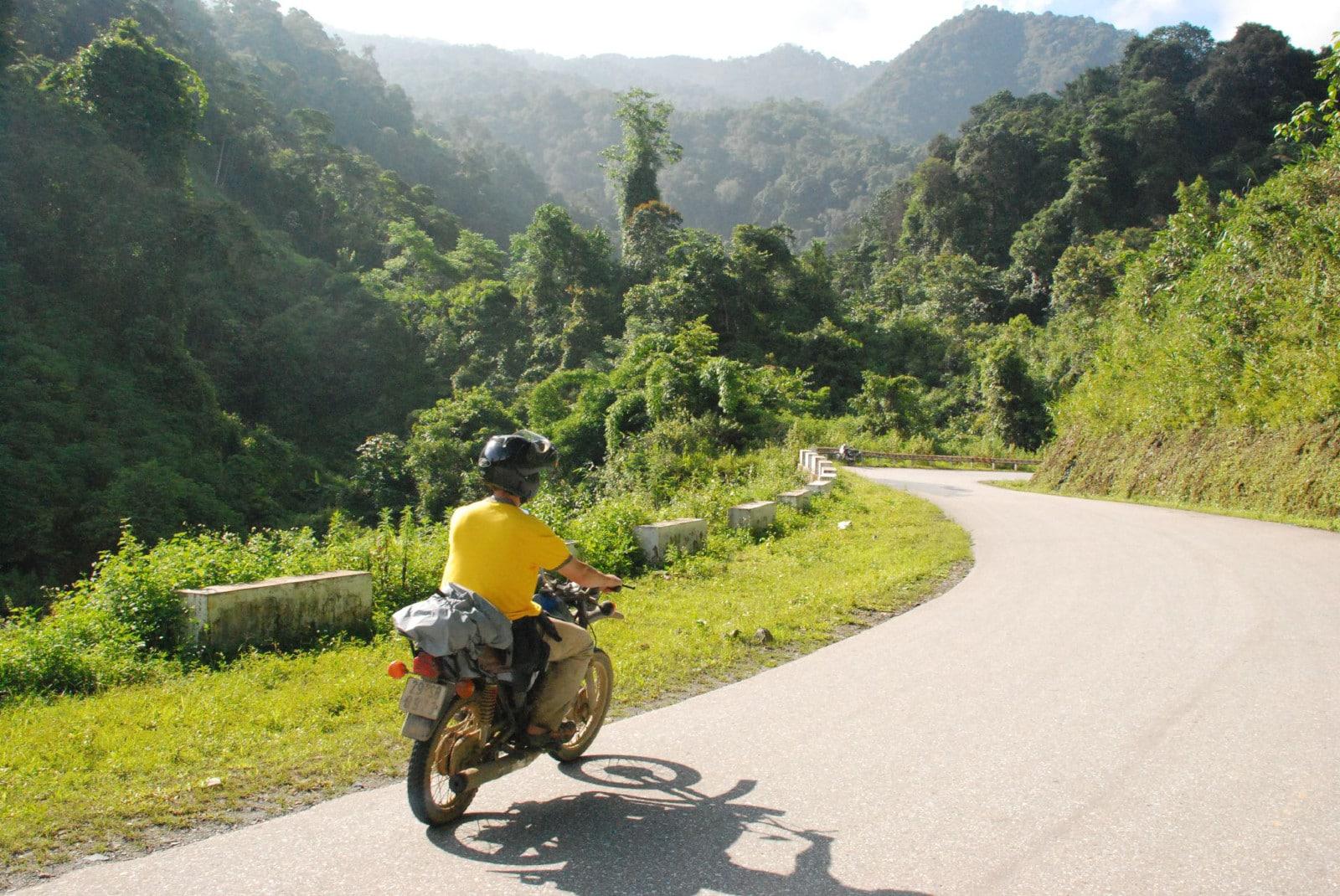 Image of a man in yellow on a minsk motorbike in Vietnam