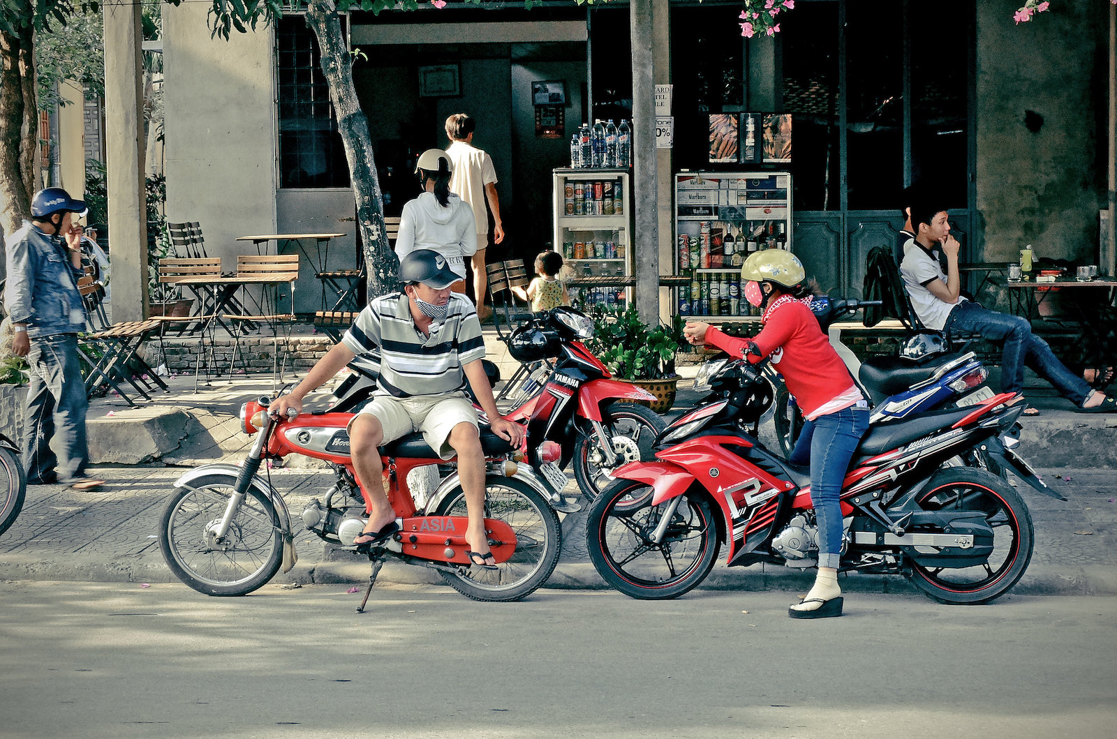 Image of two people talking on parked motorbikes in Hoi An, Vietnam