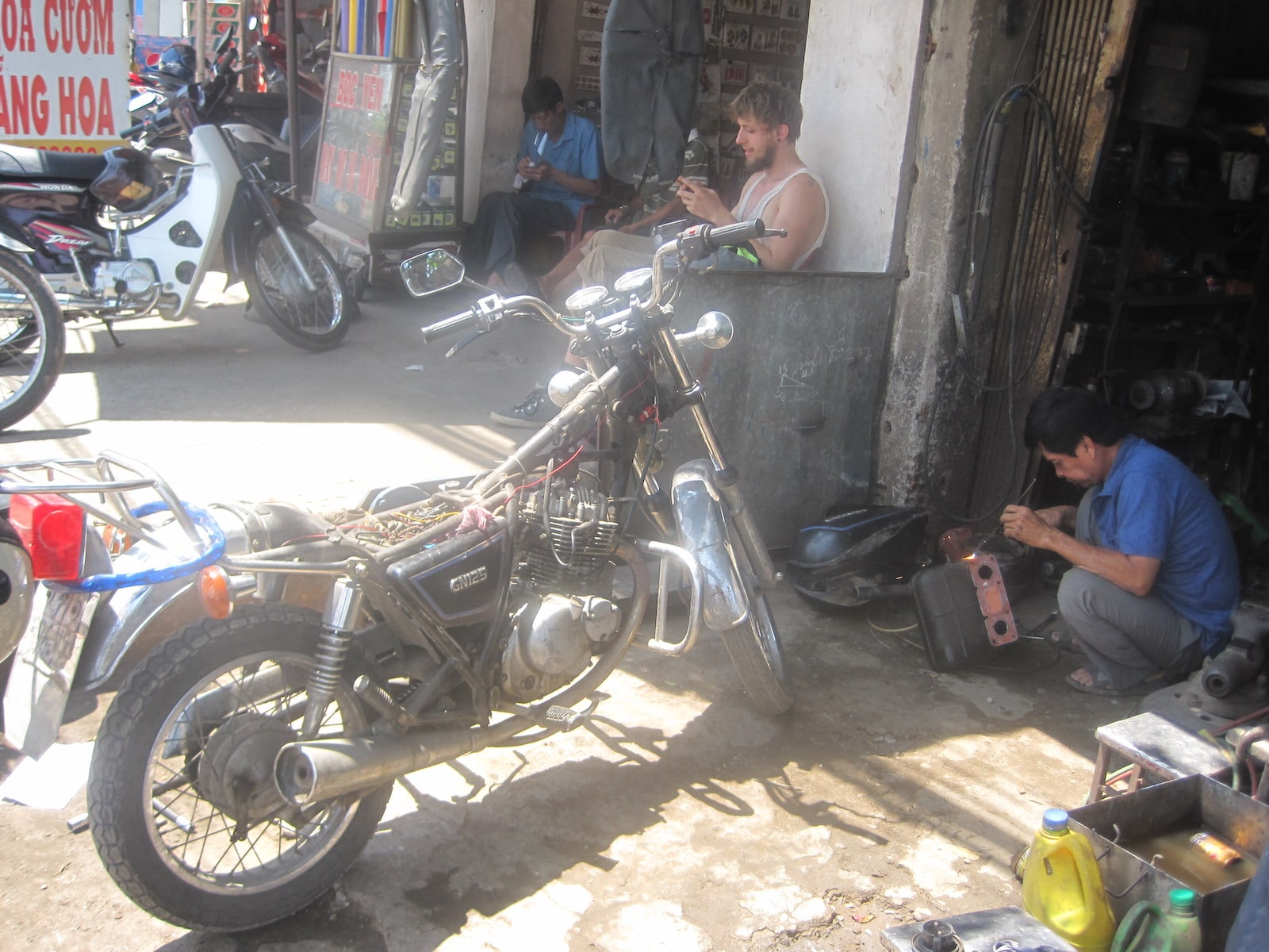 Image of a motorbike and man working on other repairs