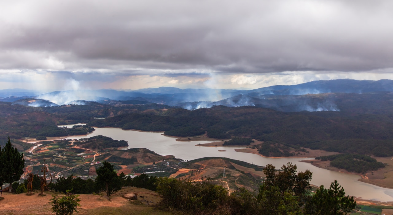 Image from the top of Langbiang Mountain overlooking Da Lat with controlled brush fires burning in the hills of Vietnam