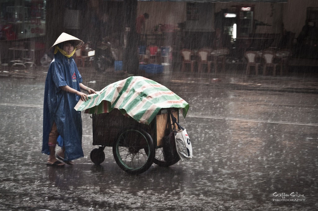 Image of a woman pushing a cart in the rain in Saigon