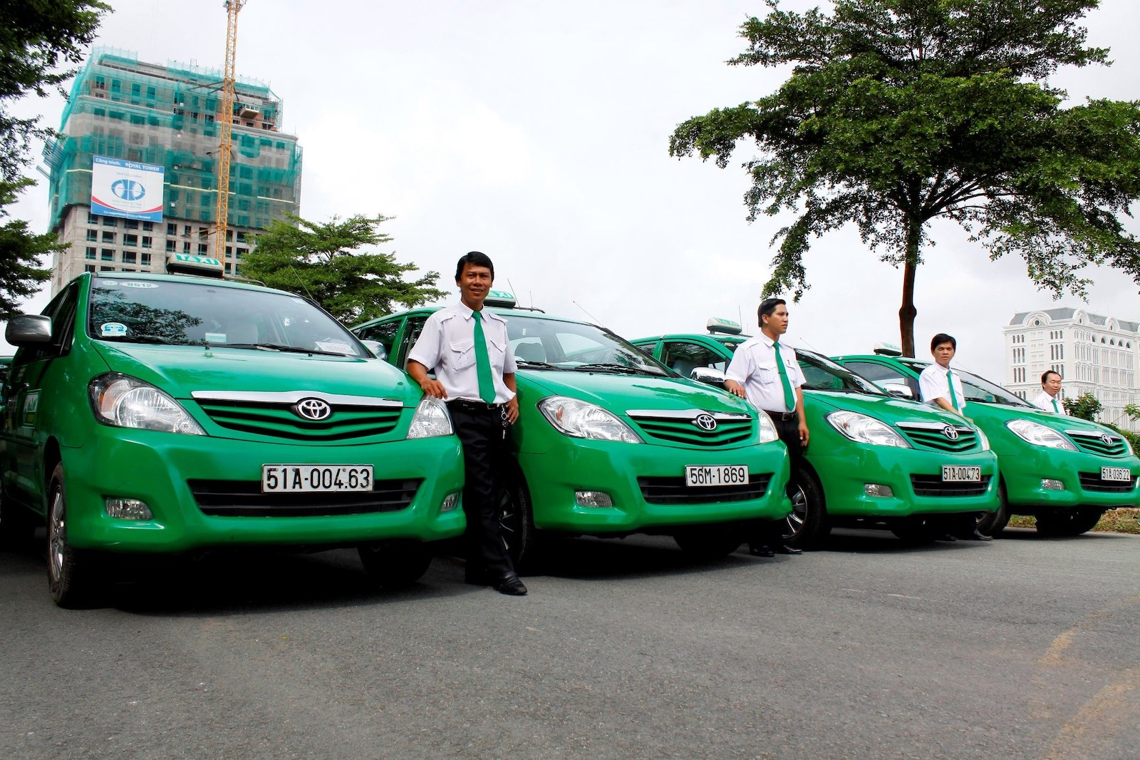 Image of Mai Linh Taxi drivers with their green cars in Vietnam