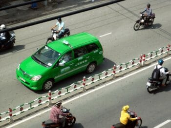 Image of a Mai Linh Taxi driving near motorbikes in Vietnam