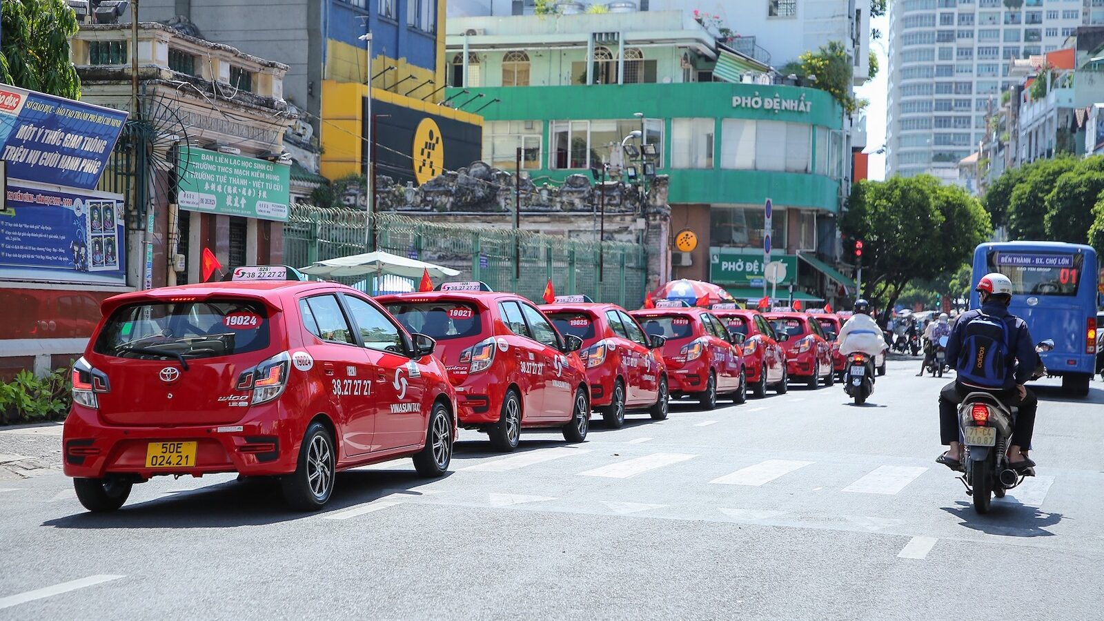 Image of a fleet of red Vinasun Taxis in Vietnam