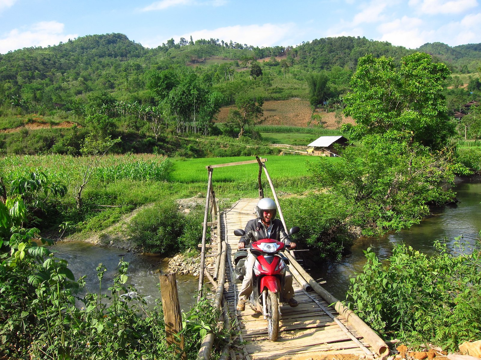 Image of a person on a motorbike crossing a bamboo bridge on the route from Meo Vac to Ba Be National Park in Vietnam
