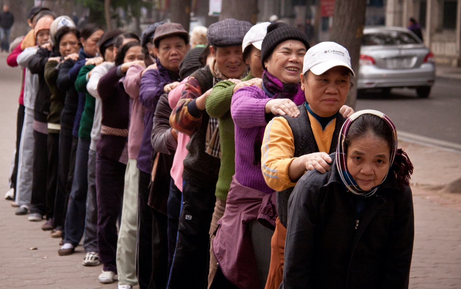Group of Vietnamese people massage each other's shoulders in Hanoi