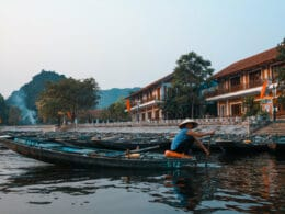 Image of a person rowing a boat near homes in Ninh Binh, Vietnam