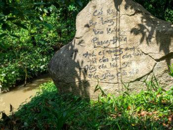 Sun shining on Vietnamese words written on rock in Mekong Delt